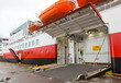 Opened side ramp gate on big passenger ferry in port