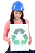 Tradeswoman holding a recycling sign