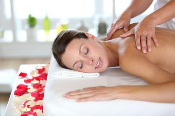 Beautiful girl receiving oil massage in beauty salon