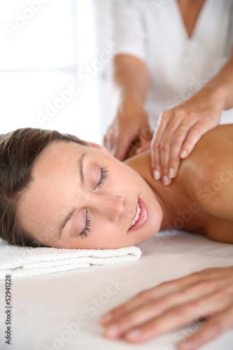 Beautiful girl receiving oil massage in beauty salon