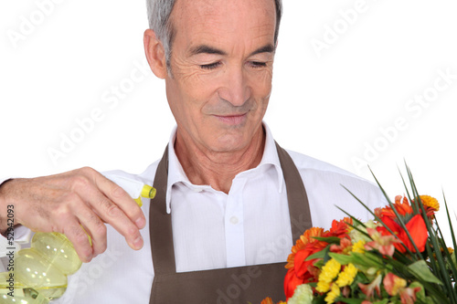 Senior man spraying water on flowers