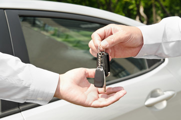 Man handing another person automobile keys new car