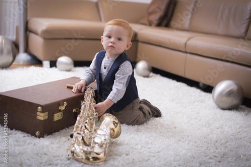 Kleiner Junge sitzt auf Teppich mit Saxophon