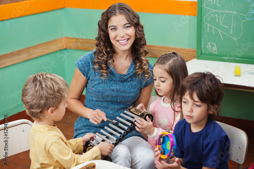 Teacher Playing Xylophone With Students In Preschool