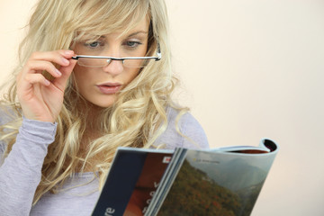 Woman with glasses reading magazine