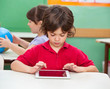 Boy Using Digital Tablet At Desk