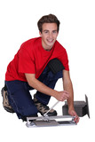 Young man using a tile cutter