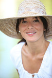 30 years old brunette wearing a straw hat and a summer dress