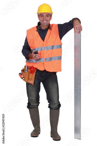 carpenter all smiles with arm resting on metallic post