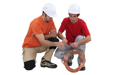 Two plumbers with copper pipe