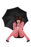 woman in striped clothing seated on the floor with umbrella