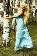 Beautiful blond woman clings to a tree in forest. flying dress
