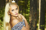 Beautiful blond woman in forest. flower in hair