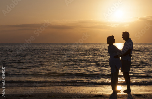 Happy Senior Couple Embracing on Sunset Beach