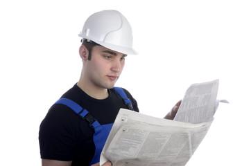 Junger Bauarbeiter liest Zeitung / Stellenangebote