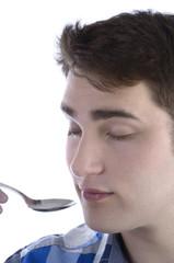 Junger Mann im karrierten Hemd riecht an Löffel