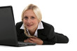 Blond woman laying with laptop