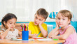 Cute preschoolers drawing with colorful pencils
