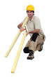 Construction worker holding wooden planks and a hammer