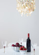 Red wine with fruits on a table, and beautiful chandelier