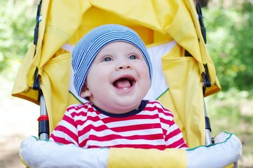 lovely smiling baby boy outdoors on yellow baby carriage