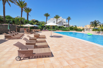 Summer day in the pool with sunbeds and parasols. Portugal Algar