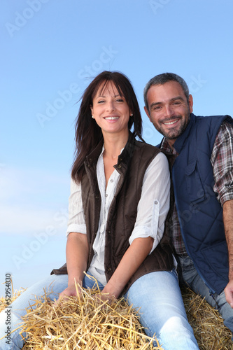 Couple sitting on haystack