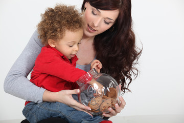 Little boy grabbing biscuit from jar