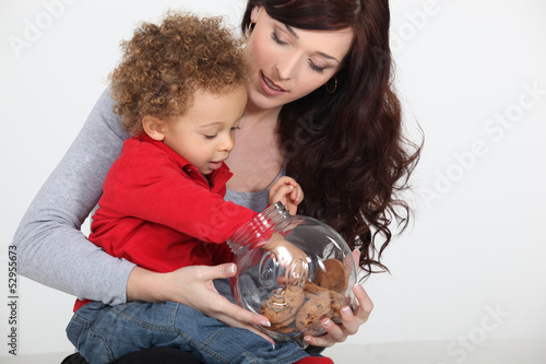 Little boy grabbing biscuit from jar