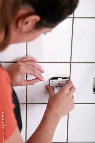Female electrician installing a jack