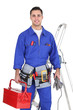 Electrician posing by his equipment