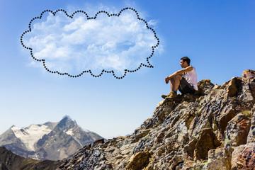 Ragazzo seduto in montagna con fumetto