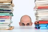 Man peeking through stacks of folders