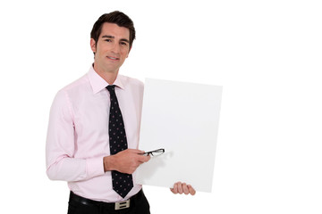 Businessman stood with blank poster