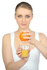 Woman squeezing fresh orange juice