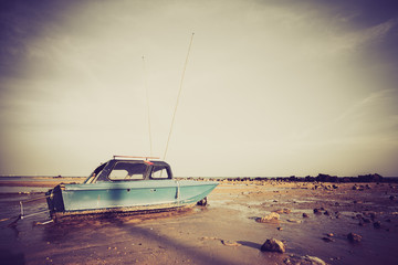 Fishing boat on sand with blue sky in retro style