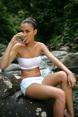 woman wearing a bikini and drinking water in the forest