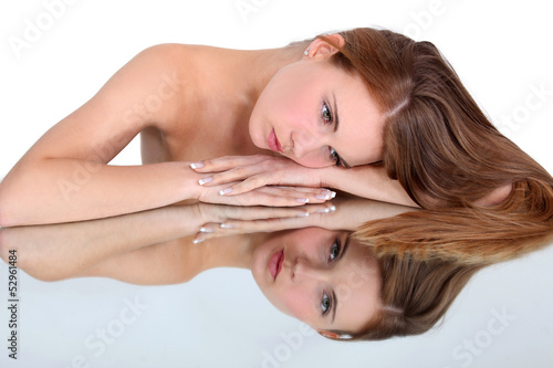 naked woman looking herself in a mirror