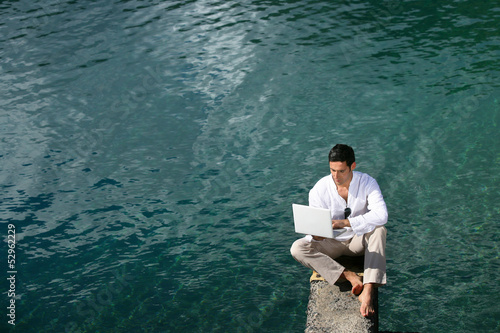 Man siting over water with a laptop