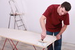 Artisan gluing wallpaper