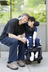 Disabled boy hugging father while waiting at hospital