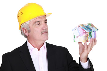 Grey-haired architect holding house made from bank notes