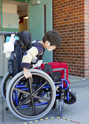Disabled kindergartener in wheelchair on playground at recess