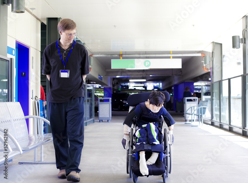 Father walking with disabled son in wheelchair to the hospital