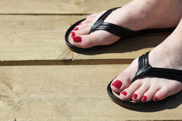 Female feet with flip-flops red nail