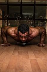 male bodybuilder doing push ups at the floor