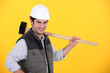 Happy builder carrying sledge-hammer
