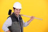 Happy builder carrying sledge-hammer