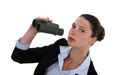 Curious businesswoman holding pair of binoculars