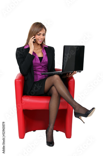 Businesswoman sitting in chair with laptop